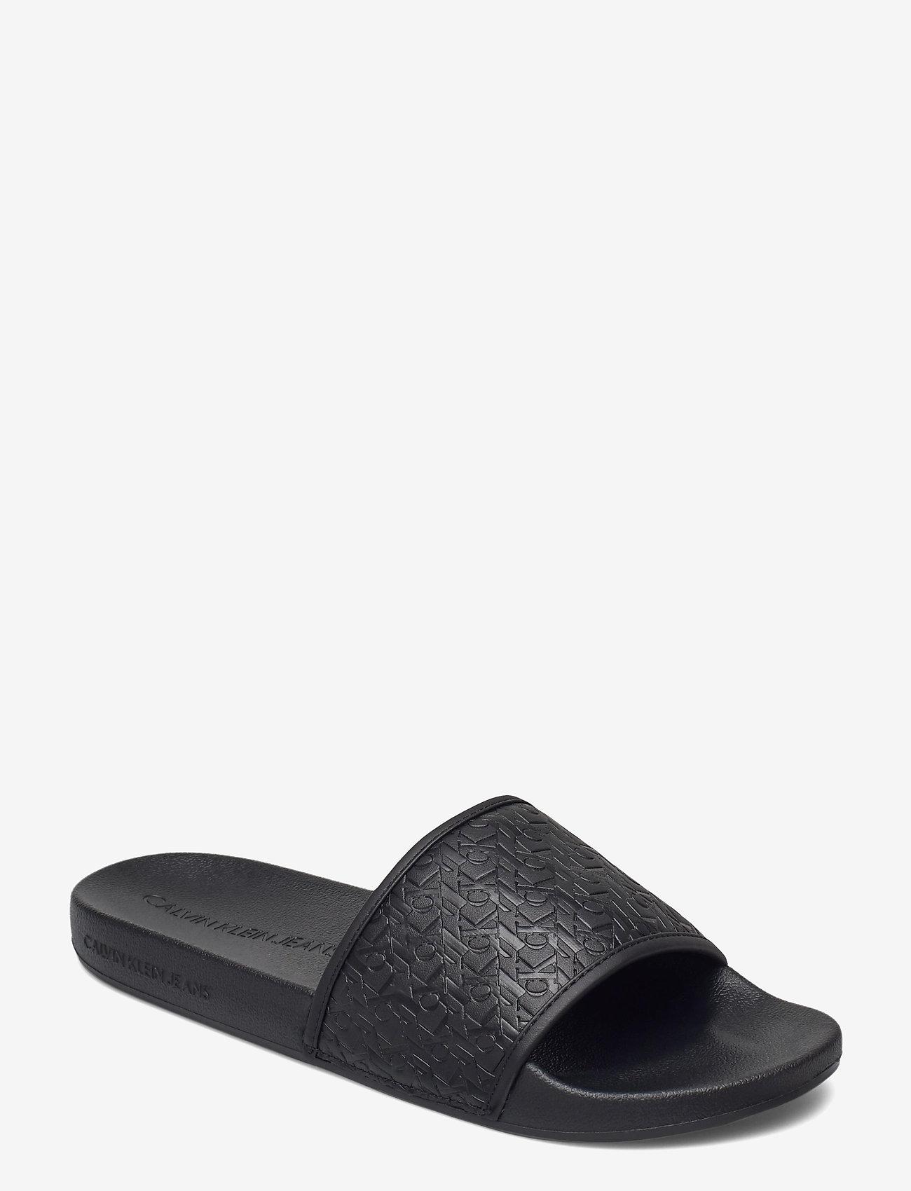 Calvin Klein - SLIDE AOP EMBOSSED PES-PU-CO - pool sliders - black - 0